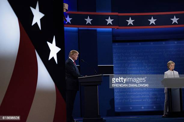 TOPSHOT Republican presidential nominee Donald Trump and Democratic presidential nominee Hillary Clinton listen to the opening question in their...