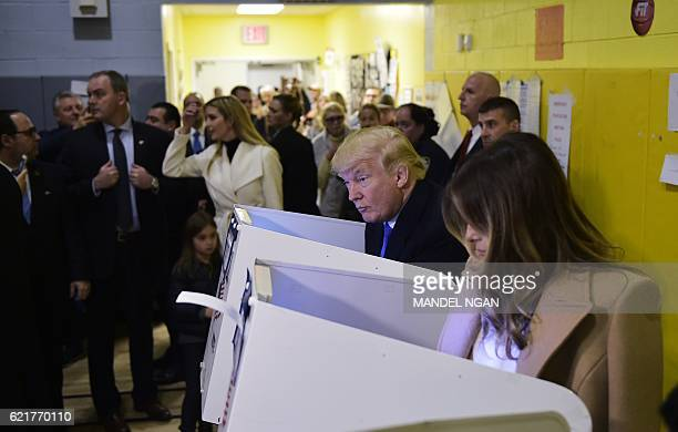 TOPSHOT Republican presidential nominee Donald Trump and his wife Melania fill out their ballots at a polling station in a school during the 2016...