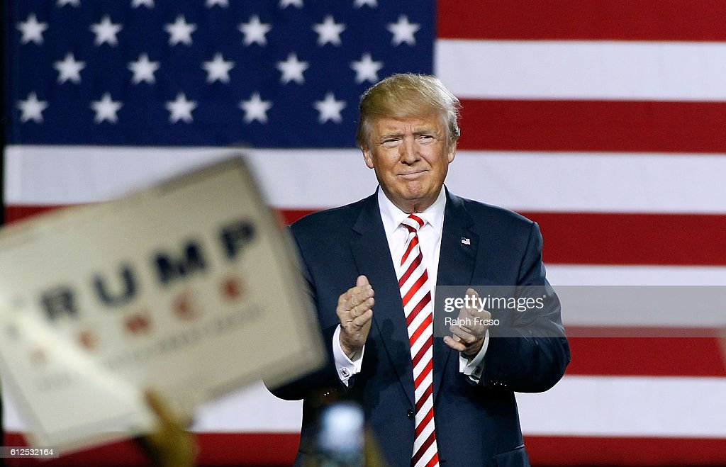 Republican presidential nominee Donald Trump applauds the crowd of supporters as he arrives at a campaign rally on October 4, 2016 in Prescott Valley, Arizona. Trump spoke in Arizona ahead of tonights vice-presidential debate.