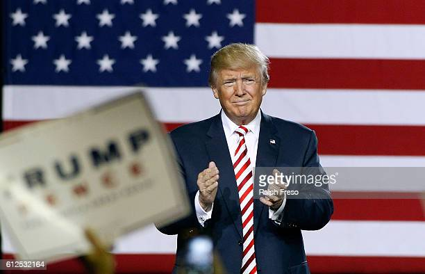 Republican presidential nominee Donald Trump applauds the crowd of supporters as he arrives at a campaign rally on October 4 2016 in Prescott Valley...