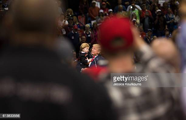 Republican presidential nominee Donald Trump brings a child from the audience on stage at a campaign rally on October 10 2016 in WilkesBarre...