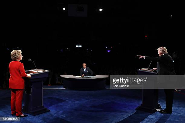 Republican presidential nominee Donald Trump debates Democratic presidential nominee Hillary Clinton as Moderator Lester Holt looks on during the...