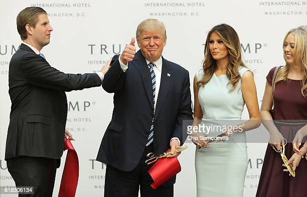 Republican presidential nominee Donald Trump gives a thumbs up after cutting the ribbon at the new Trump International Hotel with his son Eric Trump...