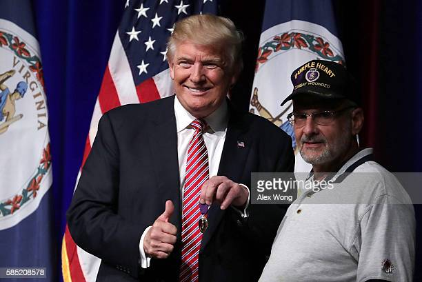 Republican presidential nominee Donald Trump greets veteran Louis Dorfman , who gave Trump his Purple Heart, during a campaign event at Briar Woods...
