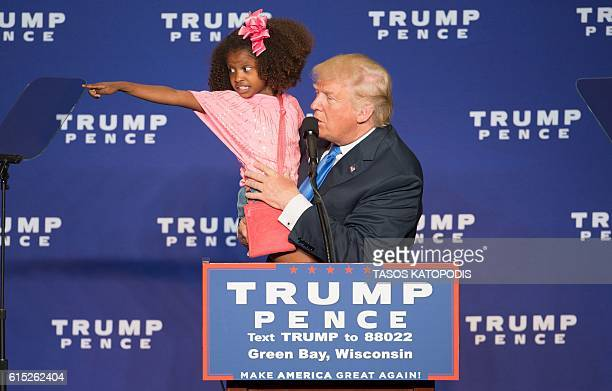 Republican presidential nominee Donald Trump holds a child as he speaks during a rally at the KI Convention Center on October 17 2016 in Green Bay...