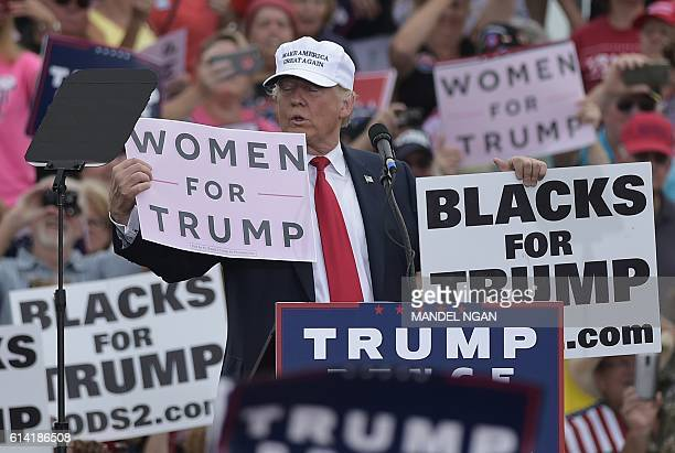 Republican presidential nominee Donald Trump holds a Women for Trump and Black for Trump placards during a rally at the Lakeland Linder Regional...
