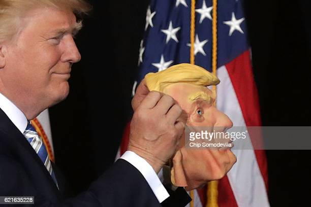 Republican presidential nominee Donald Trump holds up a rubber mask of his face during a campaign rally in the Robarts Arena at the Sarasota...