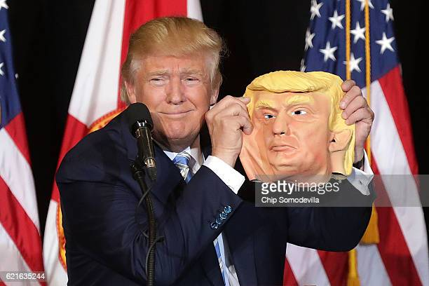 Republican presidential nominee Donald Trump holds up a rubber mask of himself during a campaign rally in the Robarts Arena at the Sarasota...