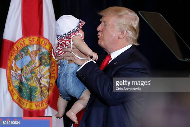 Republican presidential nominee Donald Trump kisses a baby during a campaign rally in the Special Events Center on the Florida State Fairgrounds...