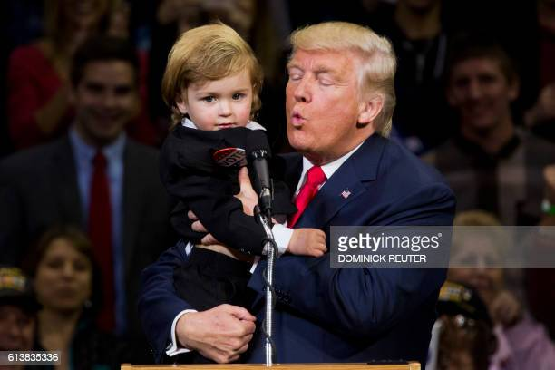 Republican presidential nominee Donald Trump kisses a child dressed as him during a rally at Mohegan Sun Arena in WilkesBarre Pennsylvania on October...