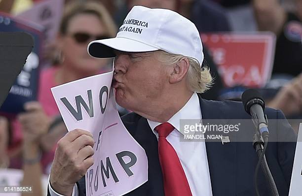 Republican presidential nominee Donald Trump kisses a Women for Trump placard during a rally at the Lakeland Linder Regional Airport in Lakeland...