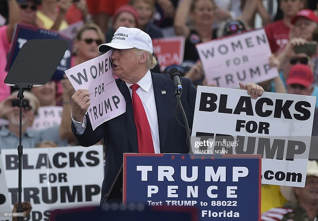 Republican presidential nominee Donald Trump kisses a 'Women for Trump' placard during a rally at the Lakeland Linder Regional Airport in Lakeland, Florida on October 12, 2016. / AFP / MANDEL
