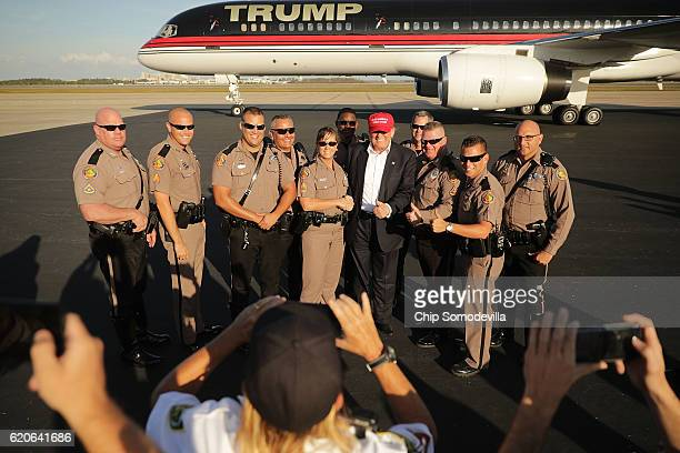 Republican presidential nominee Donald Trump poses for photographers with law enformcement officers on the tarmac at Orlando International Airport...