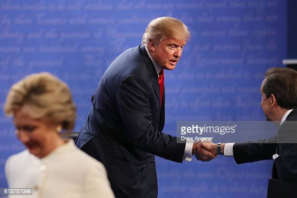 Republican presidential nominee Donald Trump shakes hands with Fox News anchor and moderator Chris Wallace as Democratic presidential nominee former...