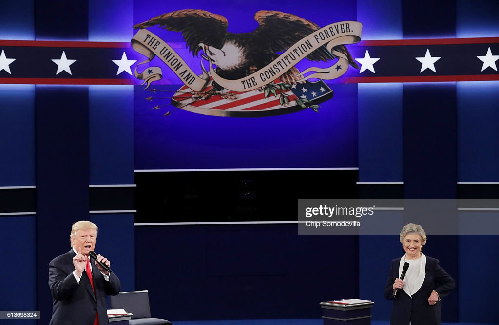 Republican presidential nominee Donald Trump (L) speaks as Democratic presidential nominee former Secretary of State Hillary Clinton smiles during the town hall debate at Washington University on October 9, 2016 in St Louis, Missouri. This is the second of three presidential debates scheduled prior to the November 8th election.