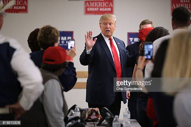 Republican presidential nominee Donald Trump talks with volunteers at a campaign phone bank before a rally at the Bank of Colorado Arena on the...