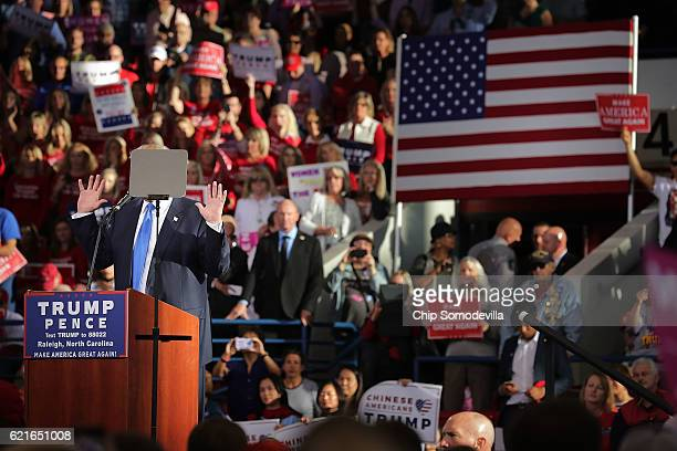 Republican presidential nominee Donald Trump's face is obscurred by a teleprompter as he holds a campaign rally at the J.S. Dorton Arena November 7,...