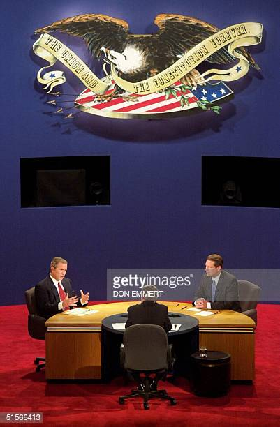 Republican presidential nominee George W. Bush answers a question from moderator Jim Lehrer as Democratic presidential nominee Al Gore listens during...