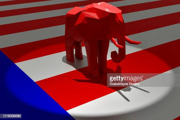 republican red elephant in spotlight on top of american flag - republican party stock pictures, royalty-free photos & images