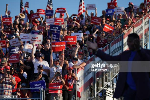 Republican Senate candidate Herschel Walker walks off the stage as a crowd cheers during a rally featuring former US President Donald Trump on...