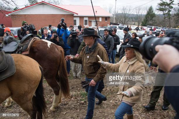 Republican Senatorial candidate Roy Moore and his wife Kayla return to their horses at the polling station after voting in Gallant AL on December 12...