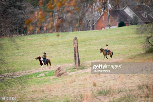 Republican Senatorial candidate Roy Moore and his wife Kayla ride their horses to the polling station to vote in Gallant AL on December 12 2017 The...