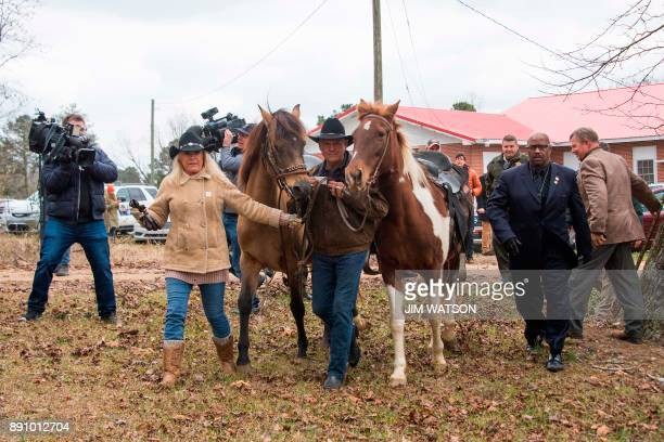 Republican Senatorial candidate Roy Moore and his wife Kayla walk their horses away at the polling station after voting in Gallant AL on December 12...