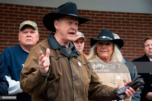 Republican Senatorial candidate Roy Moore speaks to the media as his wife Kayla looks on after arriving at a polling station in Gallant Alabama on...