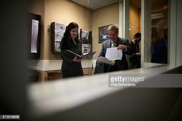 Republican Senators Kelly Ayotte and Lindsey Graham look over their notes before a news conference at the U.S. Capitol February 24, 2016 in...