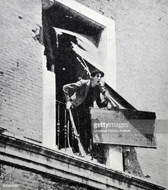 A republican soldier shouts to comrades below a window during battle in Barcelona during the Spanish civil war 1938