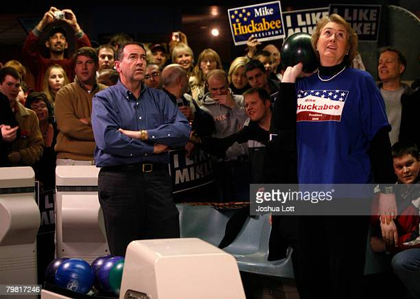 Republican U.S. Presidential hopeful and former Arkansas Gov. Mike Huckabee and his wife Janet looks up at the score monitor as they bowl during a...