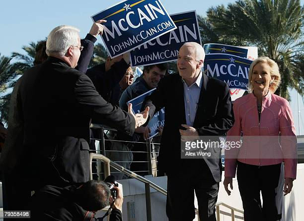 Republican US presidential hopeful and US Sen John McCain greets supporters as his wife Cindy looks on at a polling station at Mahaffey Theater...