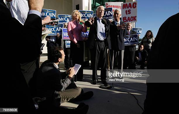 Republican US presidential hopeful and US Sen John McCain speaks to the media as his wife Cindy and Florida Gov Charlie Crist look on while they...
