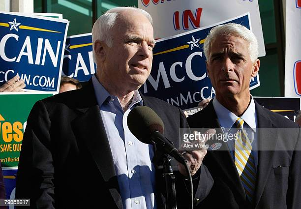 Republican US presidential hopeful and US Sen John McCain speaks to the media as Florida Gov Charlie Crist looks on as they visit a polling station...