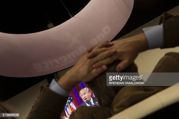 Republican US Presidential hopeful Donald Trump is seen on a screen as he speaks from a rally in Kansas during the American Conservative Union...