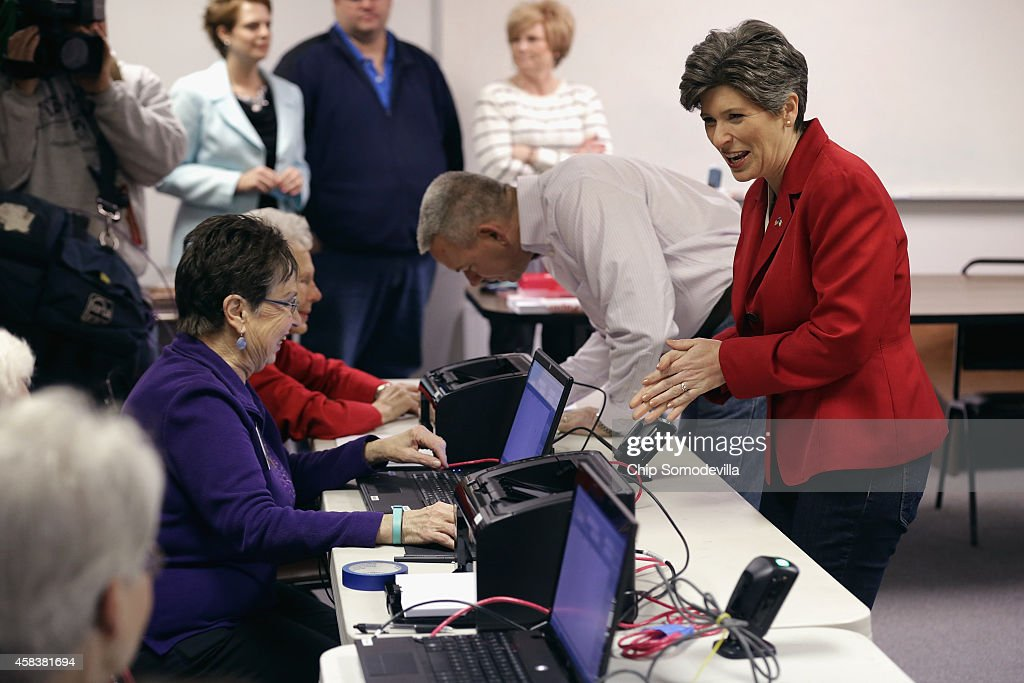 Republican U.S. Senate candidate Joni Ernst (R) and her husband Gail Ernst (C) pick up their ballots on election day at the polling place in their hometown fire department November 4, 2014 in Red Oak, Iowa. According to the polls, Ernst is in a neck-and-neck race with her opponent, Democratic candidate Rep. Bruce Braley (D-IA), and the election in Iowa could decide which party controls the U.S. Senate.