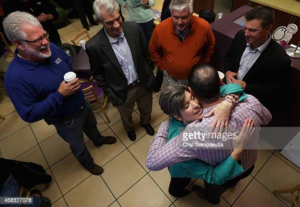 Republican U.S. Senate candidate Joni Ernst embraces a supporter as she greets customers at CJ's Bagel Basket during the kick off of her 'One More...
