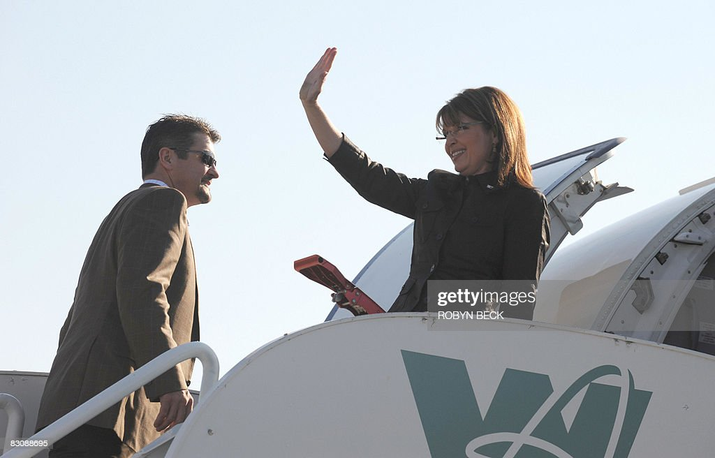 Republican vice-presidential candidate Sarah Palin waves next to her husband Todd at the Flagstaff, Arizona airport where she is boarding her campaign plane for the trip to St Louis, Missouri where she will face-off with her Democratic counterpart Joe Biden in the Vice-Presidential Debate on October 02, 2008. AFP PHOTO Robyn BECK