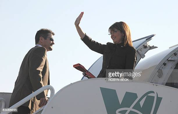Republican vicepresidential candidate Sarah Palin waves next to her husband Todd at the Flagstaff Arizona airport where she is boarding her campaign...