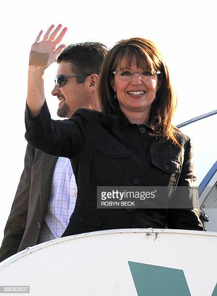 Republican vicepresidential candidate Sarah Palin waves with a bandaged hand as a result of falling while jogging as she and her husband Todd Palin...