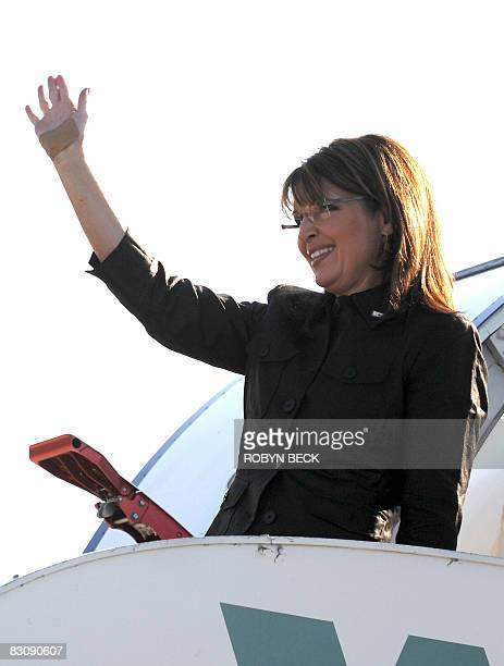 Republican vicepresidential candidate Sarah Palin waves with a bandaged hand as a result of falling while jogging as she boards her campaign plane...