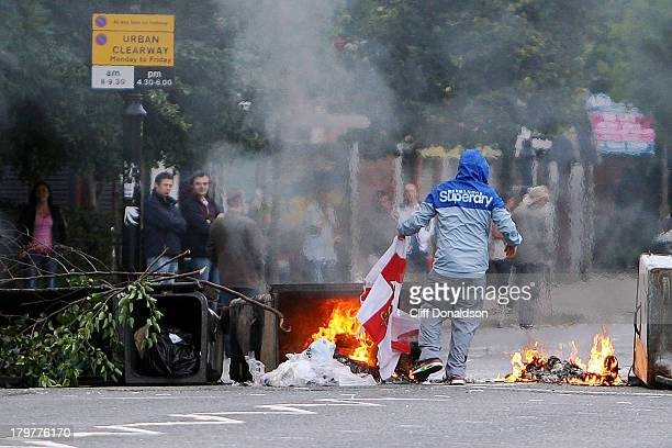 CONTENT] A republican youth attempts to burn an Ulster flag to provoke a response from onlookers during disturbances at the Ormeau Road in Belfast...