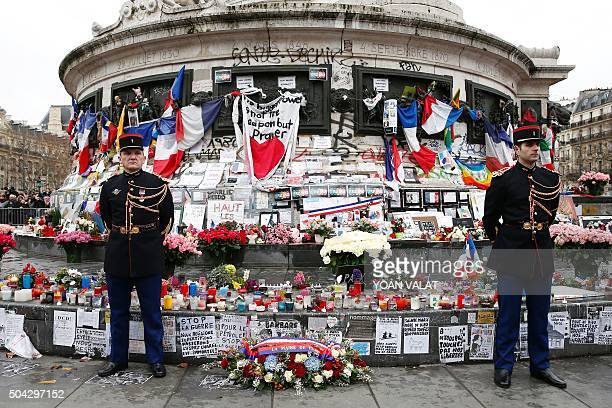 Republicans guards stand beside a wreath of flowers placed by Paris' mayor and the French president at the foot of the Statue of Marianne during a...