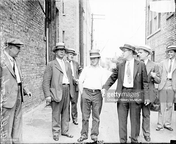 Reputed gangster Willy Doody standing with a group of men in an alley in Chicago Illinois 1929 One of the men is holding Doody's left wrist and...