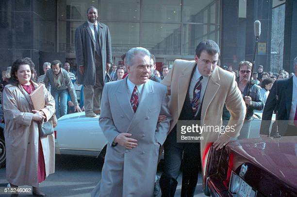 Reputed Mafia boss John Gotti is escorted by an unidentified man through the crowds outside court here 2/9 during a lunch break in his assault trial...