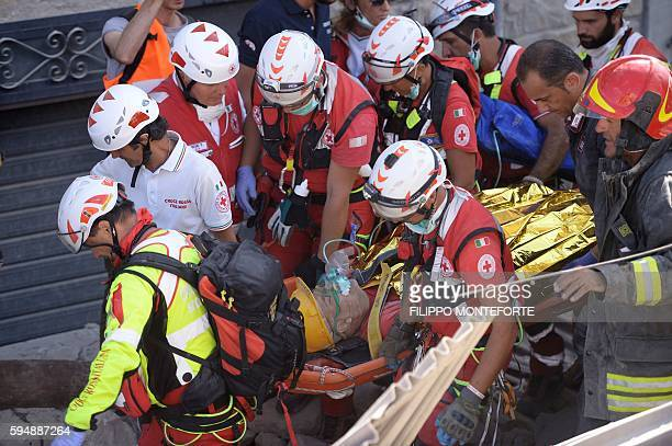 Rescue and emergency services personnel carry a survivor on a stretcher during search and rescue operations in Amatrice on August 24, 2016 after a...