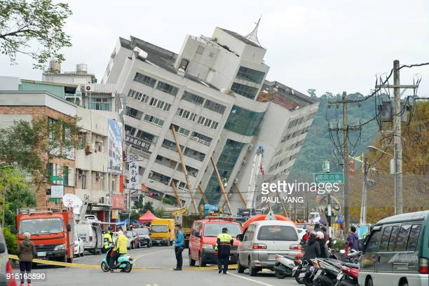 TOPSHOT Rescue and emergency workers block off a street where a building came off its foundation the morning after a 64 magnitude quake hit the...