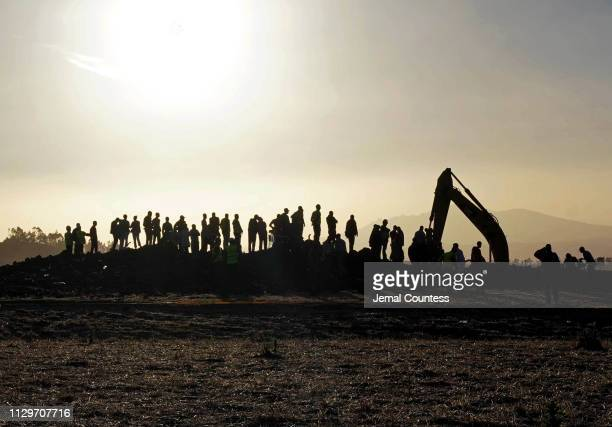 Rescue and recovery personnel use an earth mover to recover debris from a crater where Ethiopian Airlines Flight 302 crashed in a wheat field just...