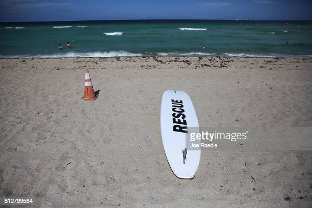 A rescue board is seen on the beach as people swim in the ocean off of Haulover Beach where a rare shark attack occured on Sunday afternoon on July...
