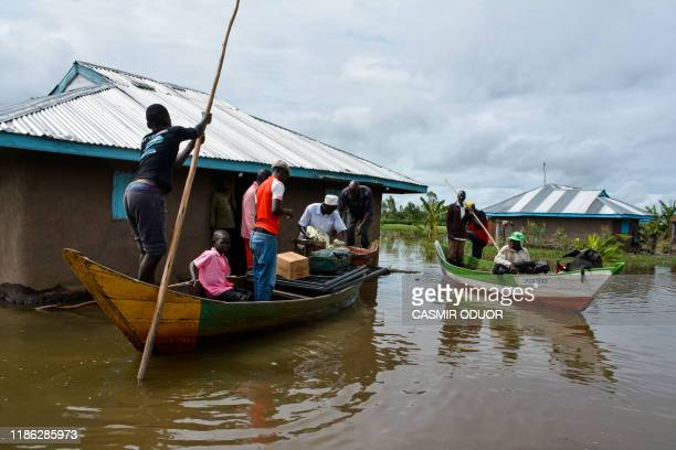 Rescue boats evacuate families after their houses were flooded in K'akola village in Nyando subcounty in Kisumu on December 3 2019 At least 210...